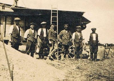 Men in front of threshing machine