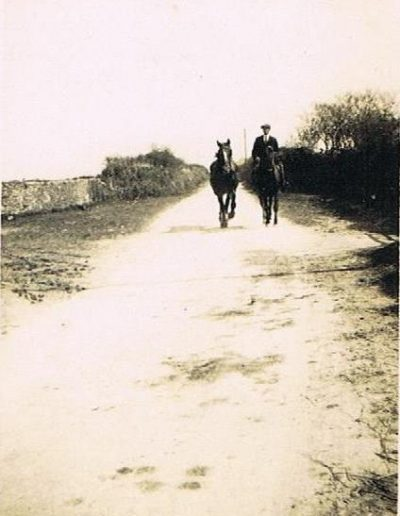 Unknown on a horse leading a second horse towards High House Farm