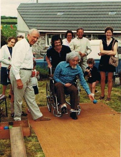Prawle Fair, Graham Fisher bought Pigs Nose off John Ireland; Alan Knight in wheelchair bowling on small green by shop, son in law behind, Jack Rendell at the side (Joan Bailey's father), 1970s