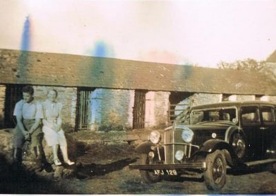 Cowshed at Lower House Farm with John Francis and Molly Tucker sitting with a car Morris Oxford,  registration AFJ 129. Laid up in the Town Linhay during the war but various children wrecked it