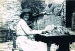 Winnie Easterbrook in glasses and sunhat, possibly bunching spring onions at Town Farm