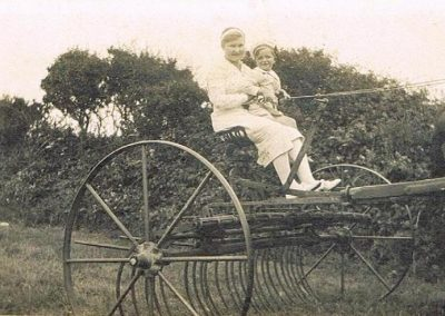 Edith Sawtell/Thorpe with ?Diana her daughter on hay rake early 1920s