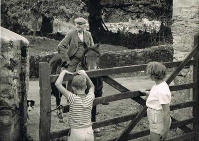 Wreford Baker riding at NorthernTown Farm, South Allington, at a gate with two children the other side of the gate ?Michael and Lorraine Trant