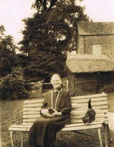 Edward Baker's granny Baker (?name) sitting with two cats in front of Manor Farm entrance gate