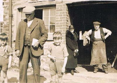 At the Forge - Philip Putt, ?Mrs Philip Putt, with grandsons Ashley and Elwyn Ford. Also Charlie Yalland (Uncle to Ashley & Elwyn), village blacksmith 1937