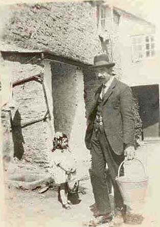 Iris Brialey (nee Hannaford) aged 3 (1925) with her grandfather George Hannaford outside no 1 Corner Cottages East Prawle green. The wooden square on the wall used for carrying buckets of water