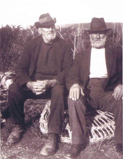 Robert A Phillips on the left, Bob Login on the right Sitting on a crab pot, Bill Login and Margaret Mitchelmore's grandfather). People.