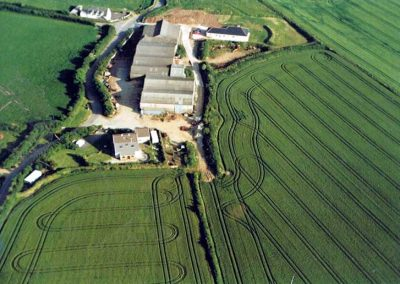 Higher House Farm with barns and surrounding fields, the school building in the background circa 1996