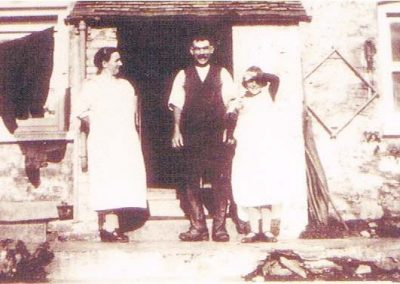 Bill and Lottie Hannaford with Vera outside Crab Cottage, (known as Channel View). Square on the wall for carrying water buckets
