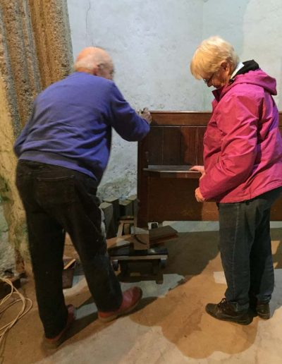 Inspecting the removal of one of the pews from the back of the Church