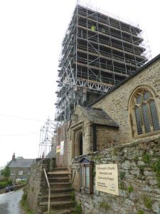 Masons working near the top of the tower